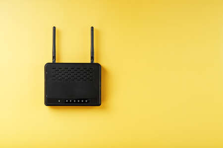 router in black on a yellow background with free space. Internet connection concept Stock Photo