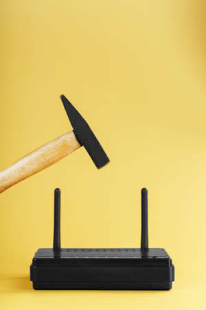 Hammer over the   router for destruction on a yellow background. Annoying internet with network connection destruction