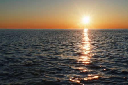 A sunny sunset on the sea stretching into the horizon with a path and highlights on the sea. Free space