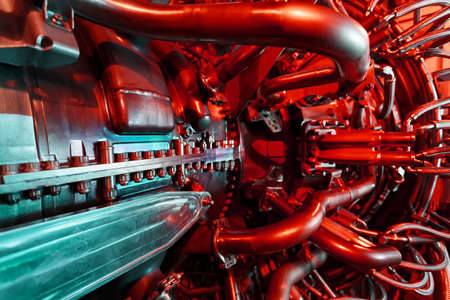 A modern gas turbine aircraft engine in a futuristic red-green light. High-tech energy of the future. Aircraft derivative, shipping and industrial turbine