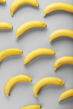 Bright pattern of yellow bananas on a gray background fashionable colors of 2021. Fruit patterns. Top view.