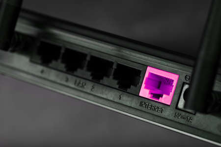 A pink patch cord is inserted into the router's WiFi port to access the Internet.