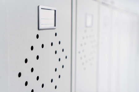 Gray metal lockers in the dressing room for clothes in a row. Storage space in the locker room Reklamní fotografie