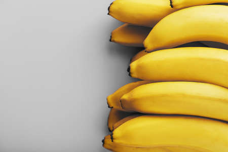 Fresh bunch of yellow bananas isolated on a Gray background. Minimalistic concept. Free space Trendy colors of 2021