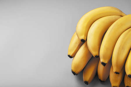 A bunch of fresh yellow bananas on a gray background in the fashionable colors of 2021. Top View. Minimalistic concept. Free space.