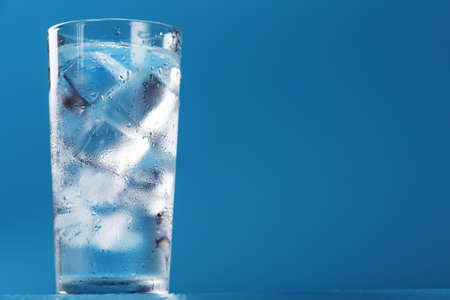 A glass with ice water and ice cubes on a blue background. A refreshing and chilling drink in hot weather. Isolate the free space. Reklamní fotografie