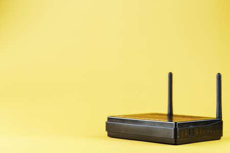 Black W-Fi router on a yellow background with free space. Isolate, top view. Online Reklamní fotografie