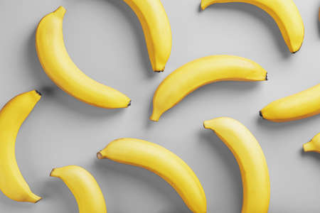 Geometric pattern of bananas on a gray background. The view from the top. Minimal flat style. Pop art design, creative summer concept.