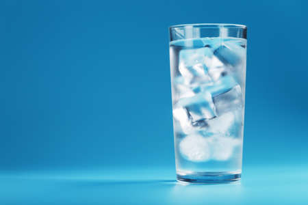 Ice cubes in a glass with crystal clear water on a blue background. Refreshing and healthy water on hot days