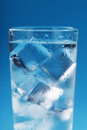 A glass with ice water and ice cubes on a blue background. A refreshing and chilling drink in hot weather. Reklamní fotografie