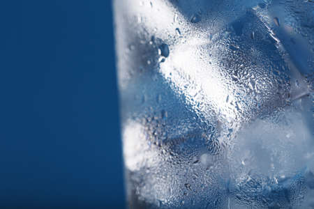 Ice cubes in a glass with crystal clear water on a blue background. Refreshing and healthy water on hot days Soft Selective Focus Reklamní fotografie