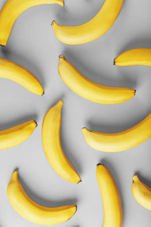 Geometric pattern of yellow bananas on a gray background in the Fashionable colors of 2021. Top view. Minimal flat style. Pop art design, creative summer concept.