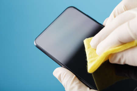 Cleaning a smartphone with a sterile yellow napkin in rubber gloves on a blue background. Disinfection and prevention of the virus