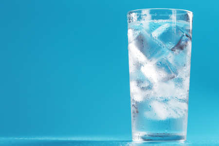 A glass with ice and clean water on a blue background. Free space, an icy drink in the sultry heat