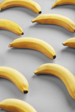 Bright pattern of yellow bananas on a gray background. View from above. Flat lay. Fruit patterns Reklamní fotografie