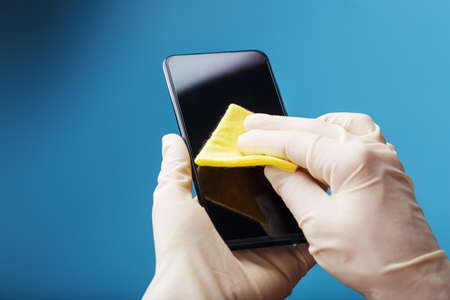 Disinfection of the smartphone with a yellow napkin with antibacterial impregnation in hand gloves. Removing virus through prevention Imagens
