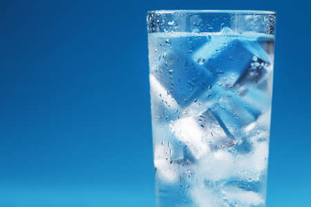 A glass with ice water and ice cubes on a blue background. A refreshing and chilling drink in hot weather. Isolate the free space. Imagens