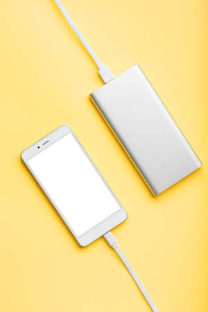 Power Bank charges your smartphone on a pink background. Universal external battery for gadgets free space and minimalistic composition. Portable charging for your smartphone.
