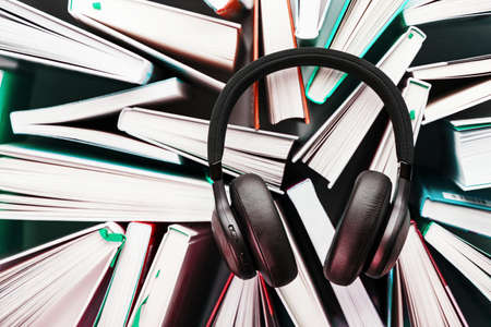 Wireless overhead black headphones lie on the books. The concept of learning through an audiobook. To listen to the book. The view from the top