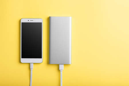 Smartphone charging with power bank by wire on yellow background.