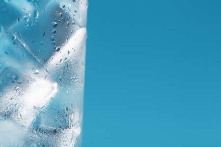 A glass with ice water and ice cubes on a blue background. Imagens