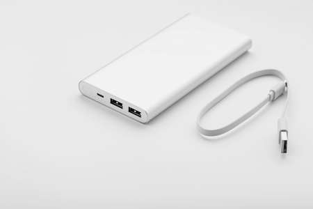 Powerbank for charging mobile devices with cable, on a white background.