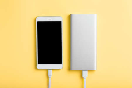 Power Bank charges a smartphone on a yellow background.