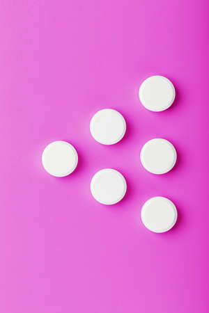 White Ecstasy pills in a row on a pink background, isolate.