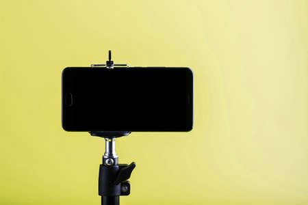 Smartphone attached to a tripod on a yellow background.