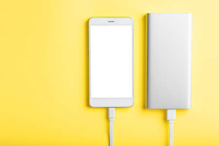 Power Bank charges a smartphone on a yellow background. Universal external battery for gadgets. Free space and minimalistic composition. View from above