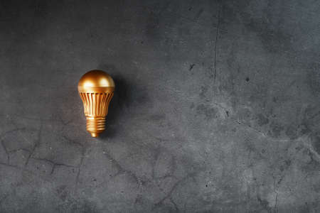 Gold light bulb on a black textured background. The concept of the idea. Free space, top view