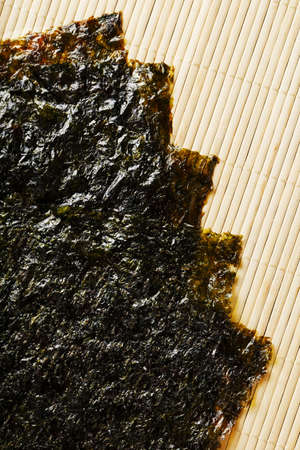 Nori algae leaves on a bamboo substrate. The main ingredient for sushi rolls. Top view