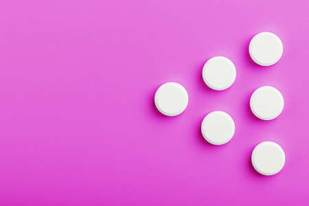 White Ecstasy pills in a row on a pink background, isolate. Top view, place for text. Imagens