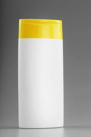 White bottle of shampoo and shower gel with yellow cap on gray background. Colors 2022. Free space