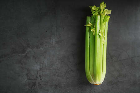 Fresh celery stalks on a black textured background. The concept of healthy vegetarian food. Free space Imagens
