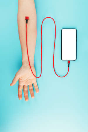 A smartphone with a large white screen is connected via a red USB cord to a vein in the hand on a blue background. The concept of drug addiction on the social networks of the Internet. Stock Photo
