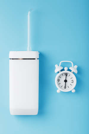 Irrigator oral cleaning with alarm clock on blue background. A mobile device for brushing your teeth and a snow-white smile. Free space