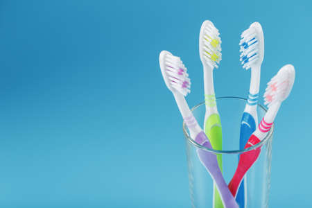 Toothbrushes of different colors in a transparent glass on a blue background. The concept of oral health care for the whole family. Free space