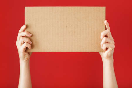 Hands holding a blank sheet of cardboard on a red background. Space for text