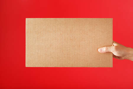 Cardboard sign in hand on a red background with free space. Space for text