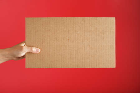 Hand holding a blank sheet of cardboard on a red background. Space for text