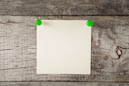 A clean note sticker on a wooden background. Space for text, free space, top view