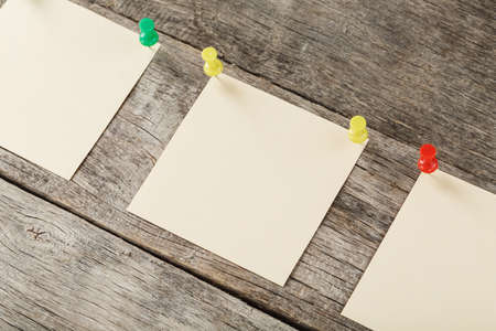 Sticky notes with pins in a row on a wooden background. Space for text, free space, top view Standard-Bild