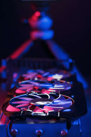 A graphics card with a row of fans with a cyanotic purple backlight in a futuristic design. Powerful gaming graphics card for video games and cryptocurrency mining. Dark key, top view
