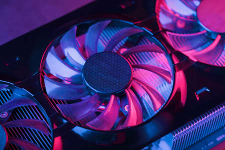 A close-up video card fan with cyanide magenta illumination in a futuristic style. Powerful gaming graphics card for video games and cryptocurrency mining. Dark Key, Close-up, Macro