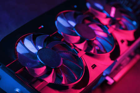Large and powerful graphics card with three fans with blue pink light. The concept of a cyberpunk video chip for gaming and cryptocurrency mining. Dark key, top view