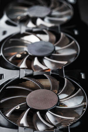 A video card with three fans is hardly a powerful cooling system. Video chip for gaming and cryptocurrency mining. Dark key Standard-Bild