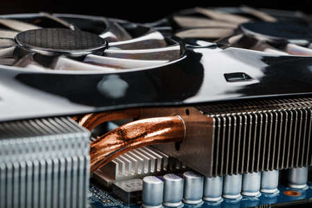 Video card with a cooling system with copper pipes, aluminum radiators and fans. Video chip for gaming and cryptocurrency mining. Dark key