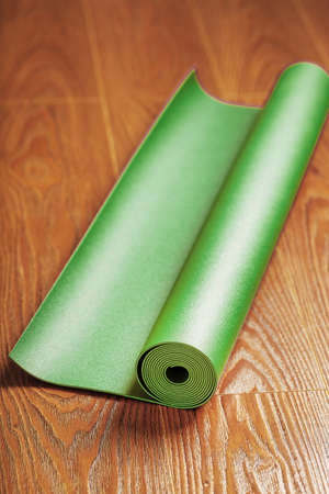 A green yoga mat is laid out in a roll on the wooden floor. A healthy lifestyle in isolation.