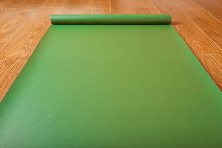 Green Yoga mat on wooden floor unfolded. Healthy lifestyle, fitness, sports. Top view.